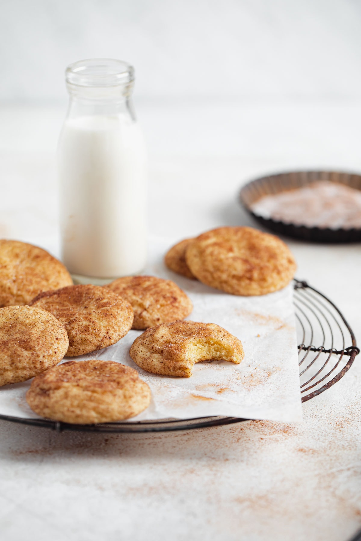 snickerdoodles on a cooling rack with a glass of milk