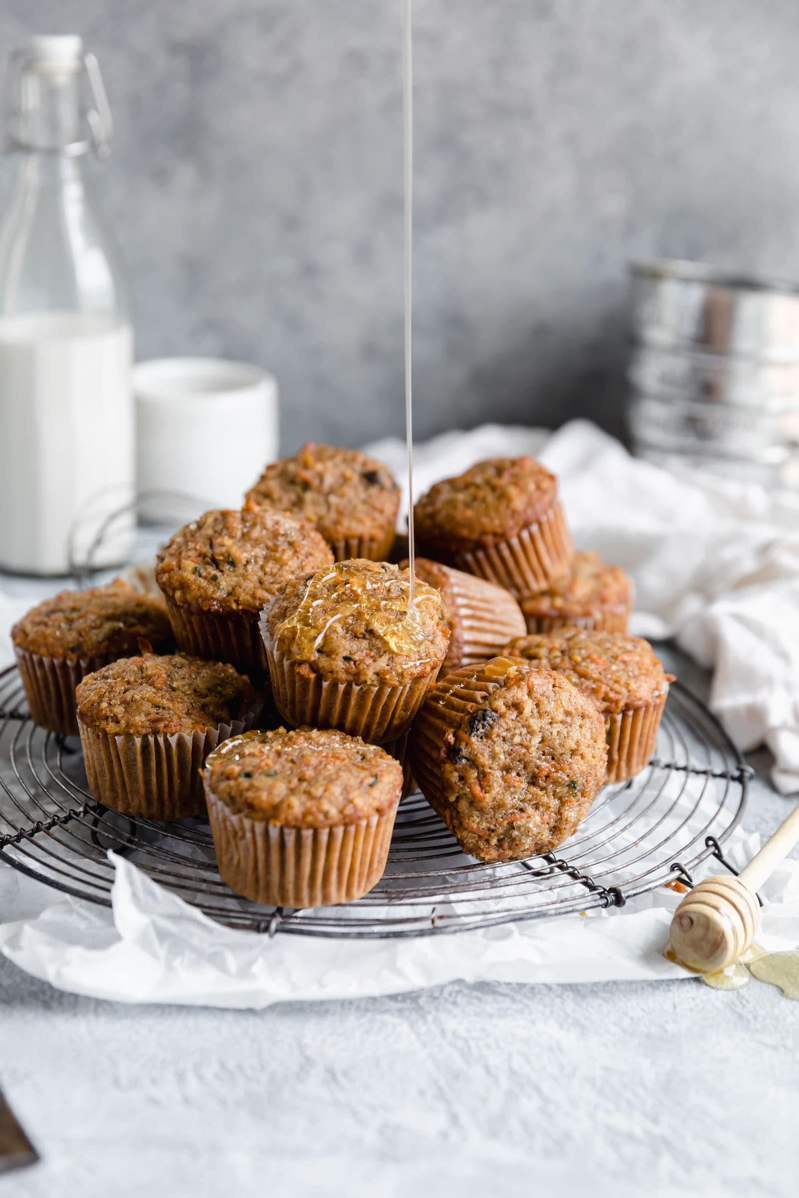 pile of morning glory muffins drizzled with honey