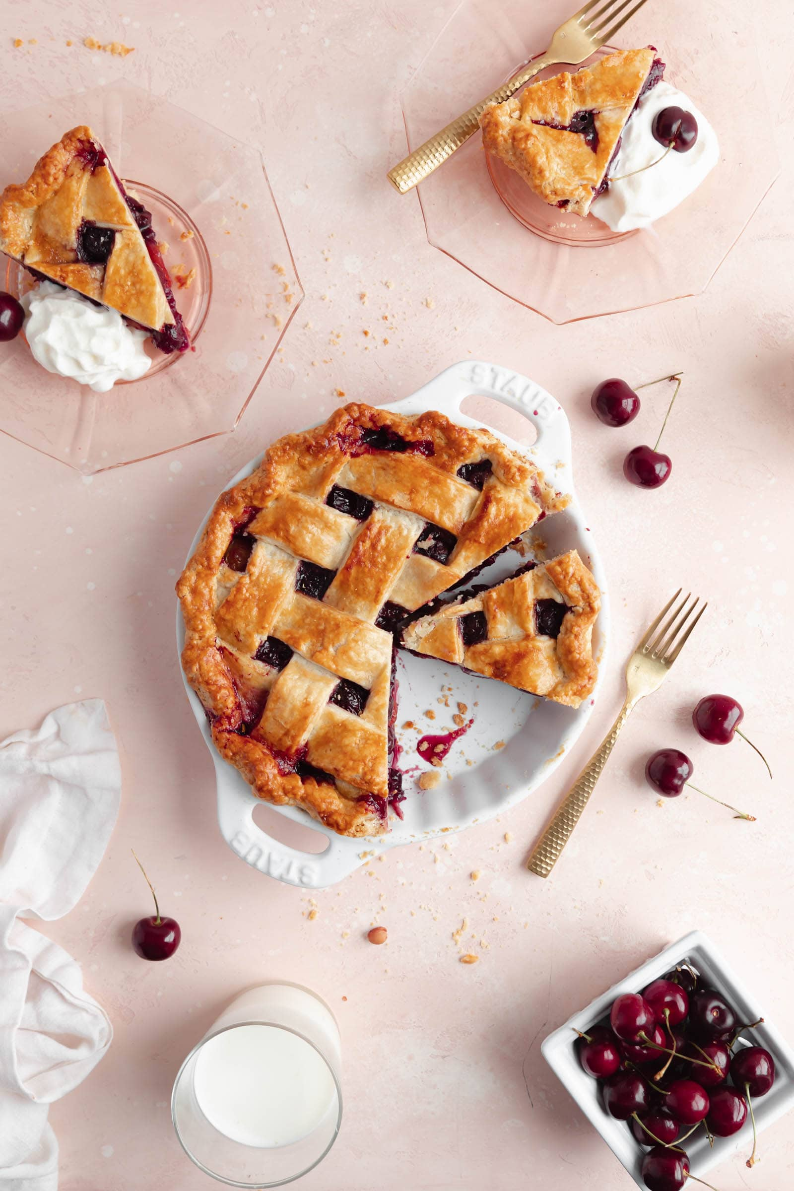 cherry pie with slices and cherries on a pink background