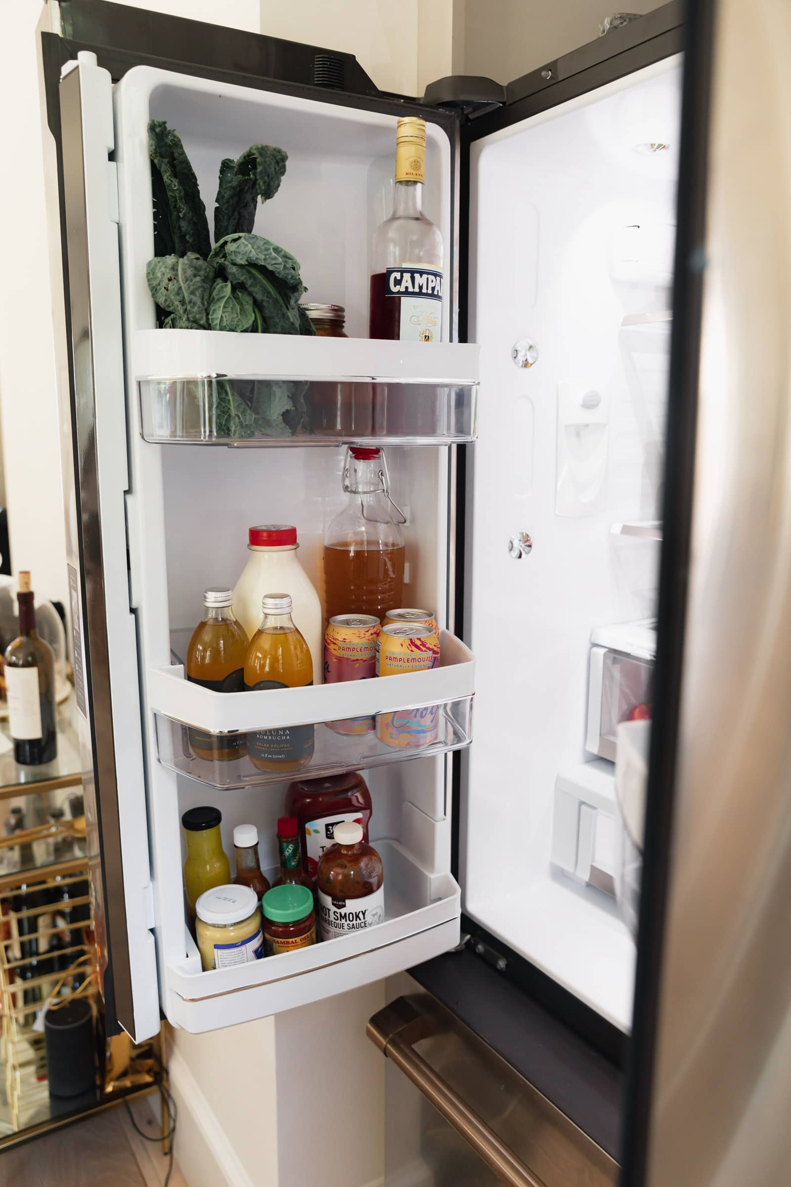 fridge door with drinks, condiments and food