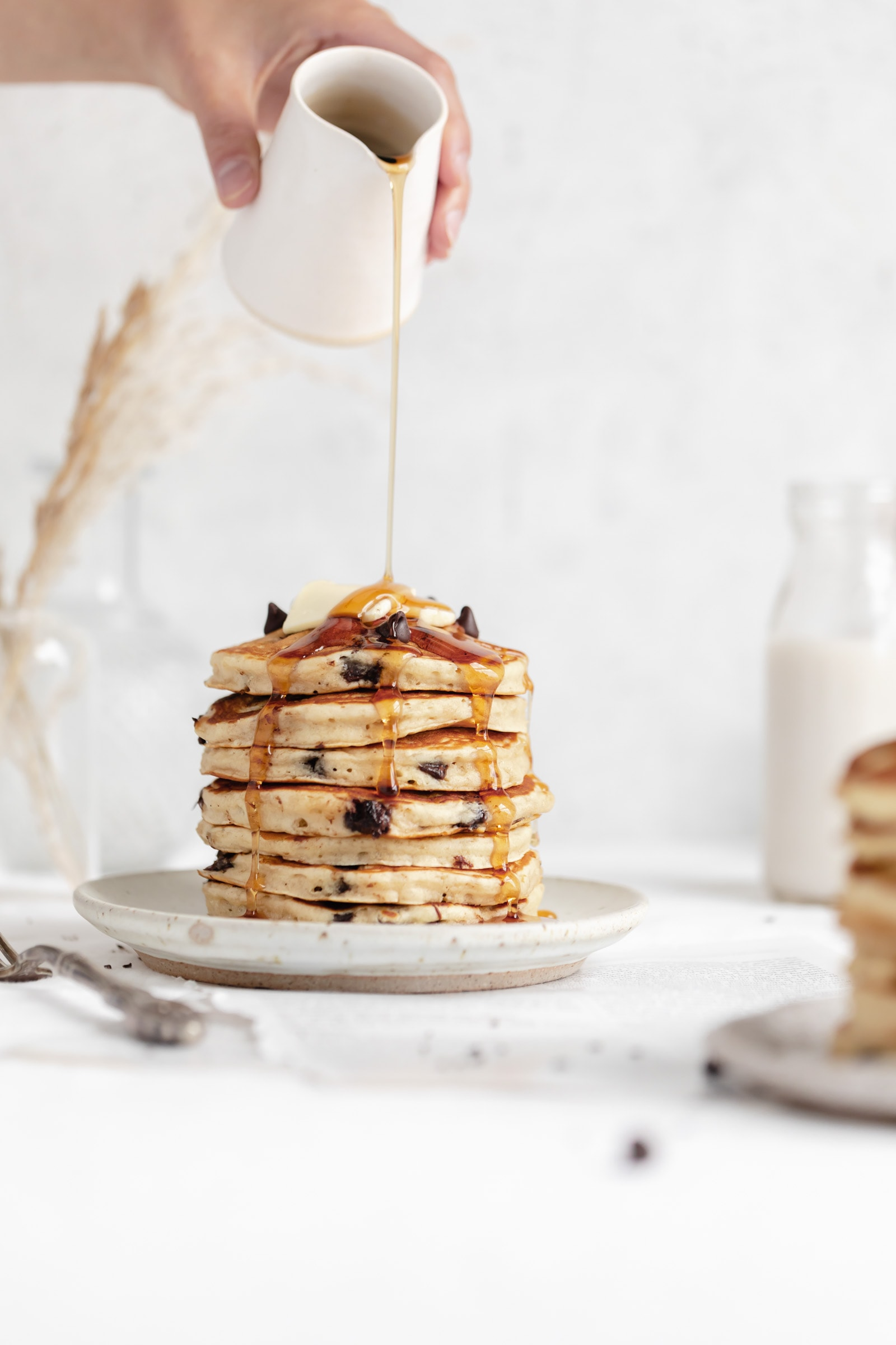 fluffy chocolate chip pancakes with maple syrup and butter
