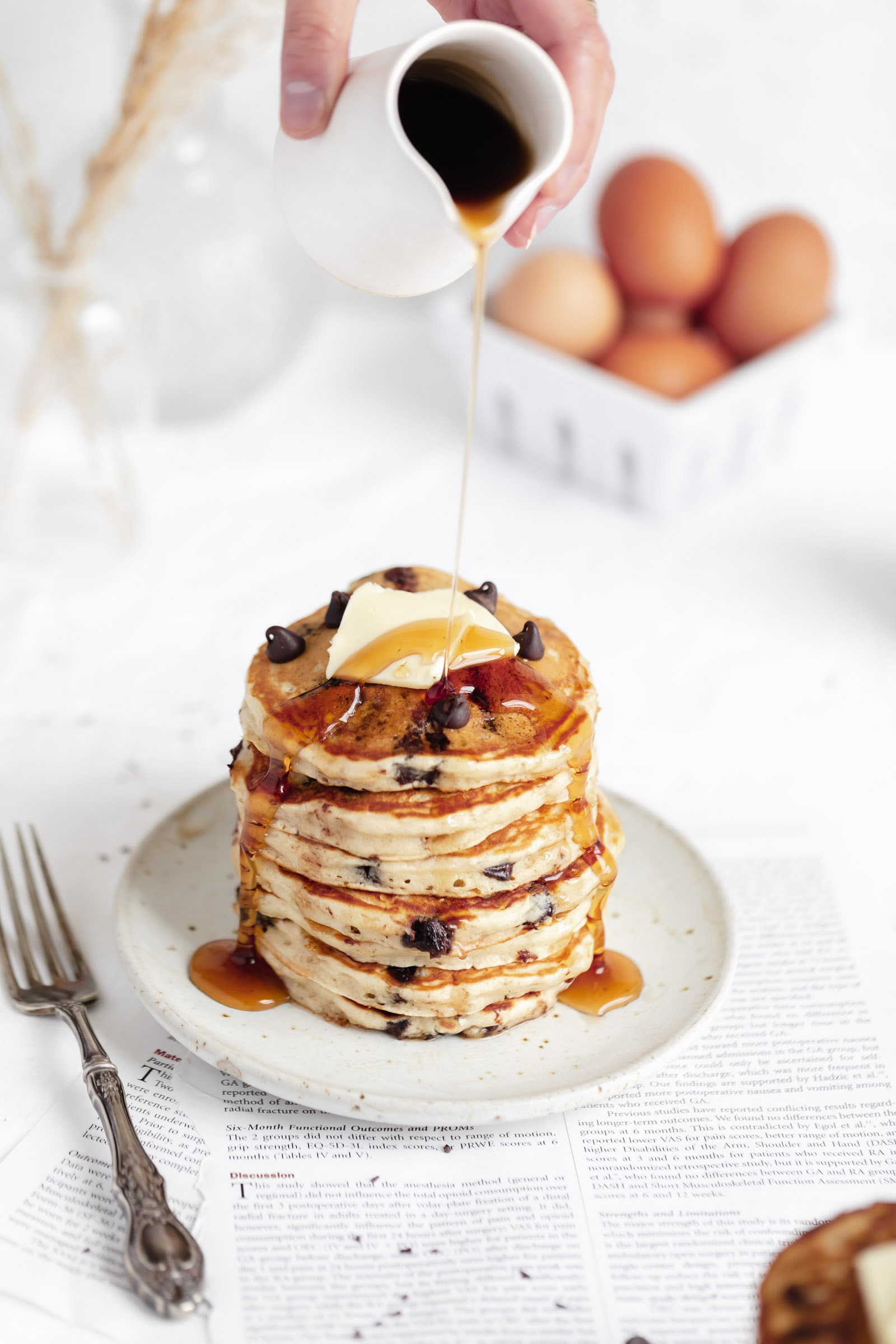 perfect chocolate chip pancakes in a stack with maple syrup