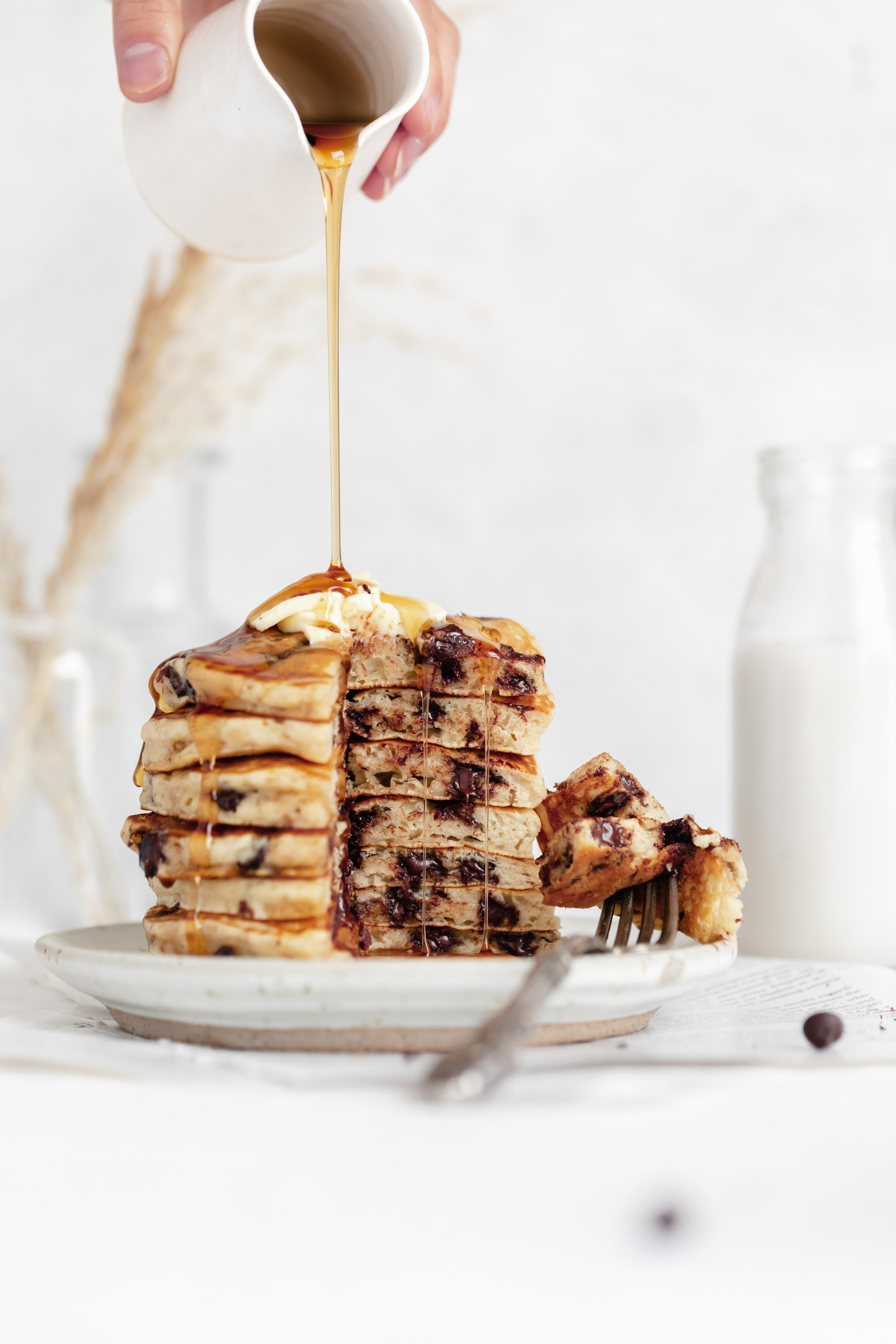 easy chocolate chip pancakes in a stack with maple syrup and butter