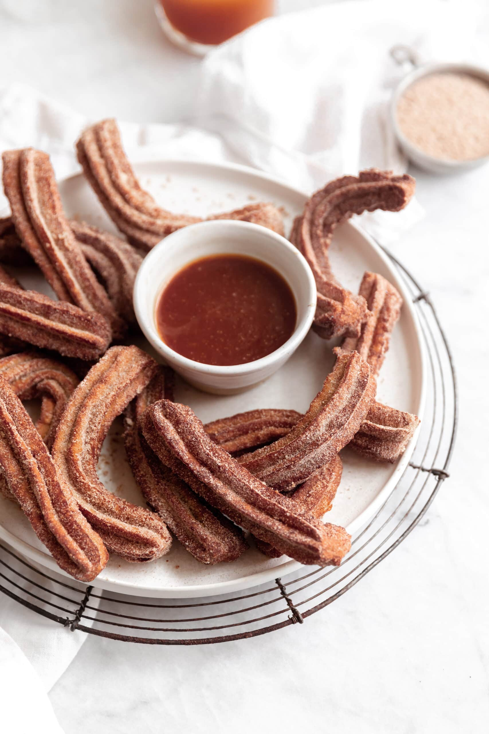 apple cider churros on a plate with caramel sauce