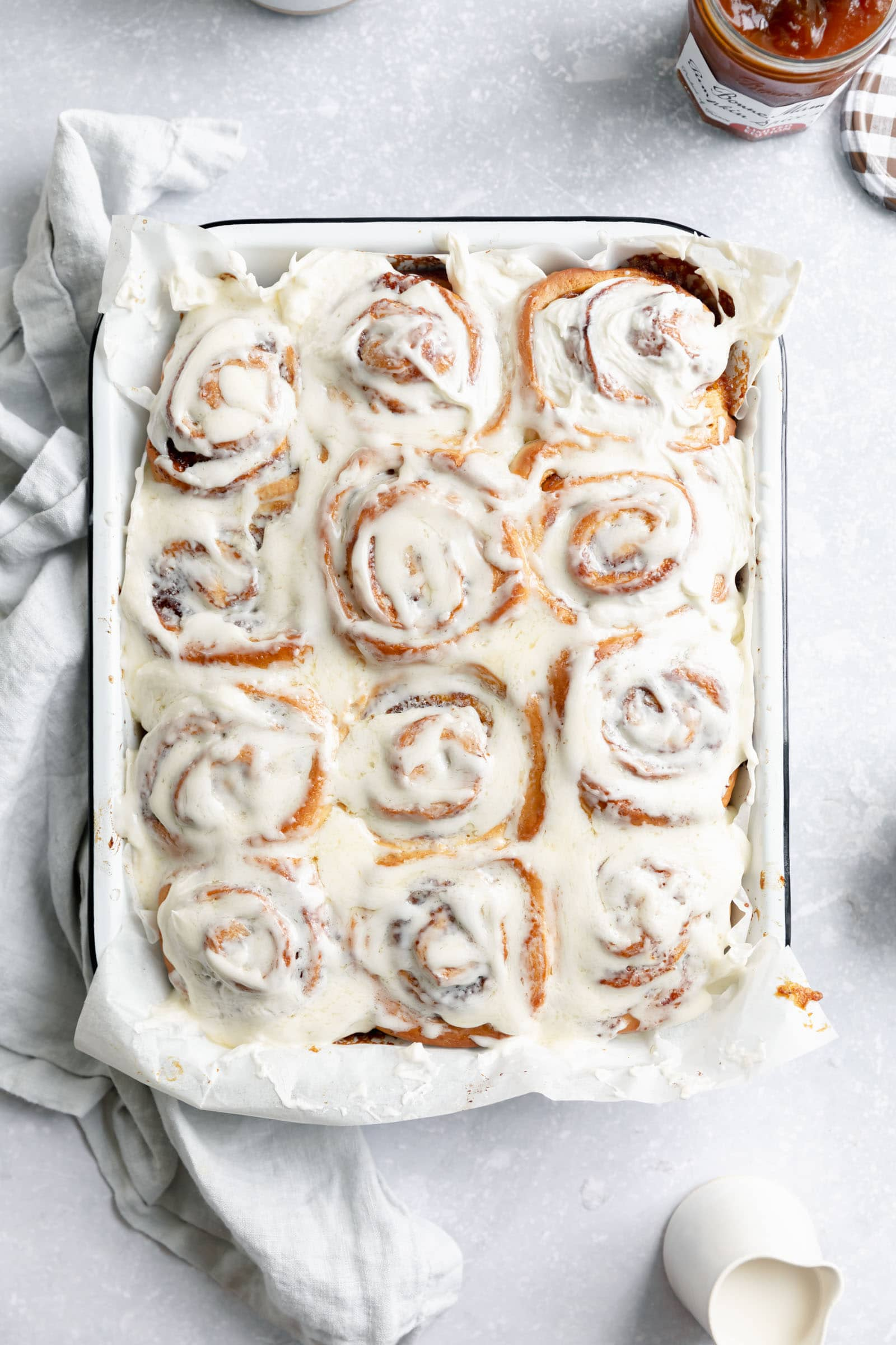 pumpkin cinnamon rolls with cream cheese icing in a pan