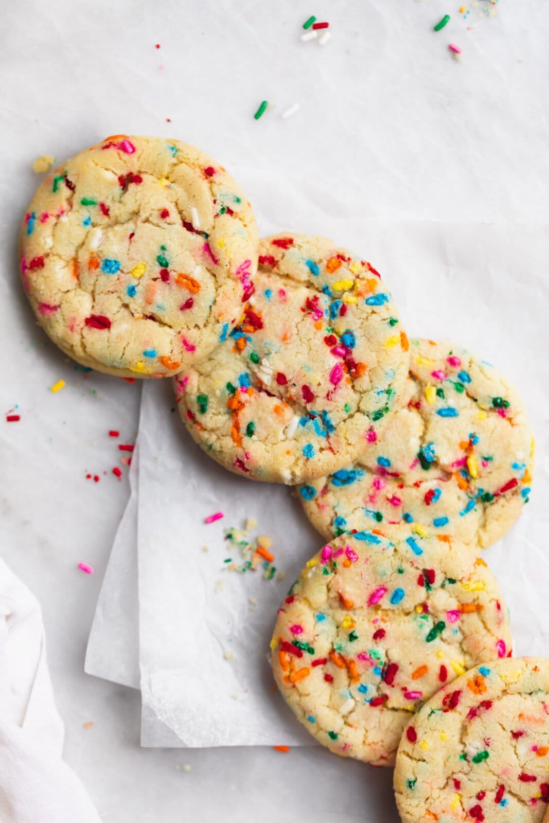 funfetti cookies in with sprinkles on parchment paper