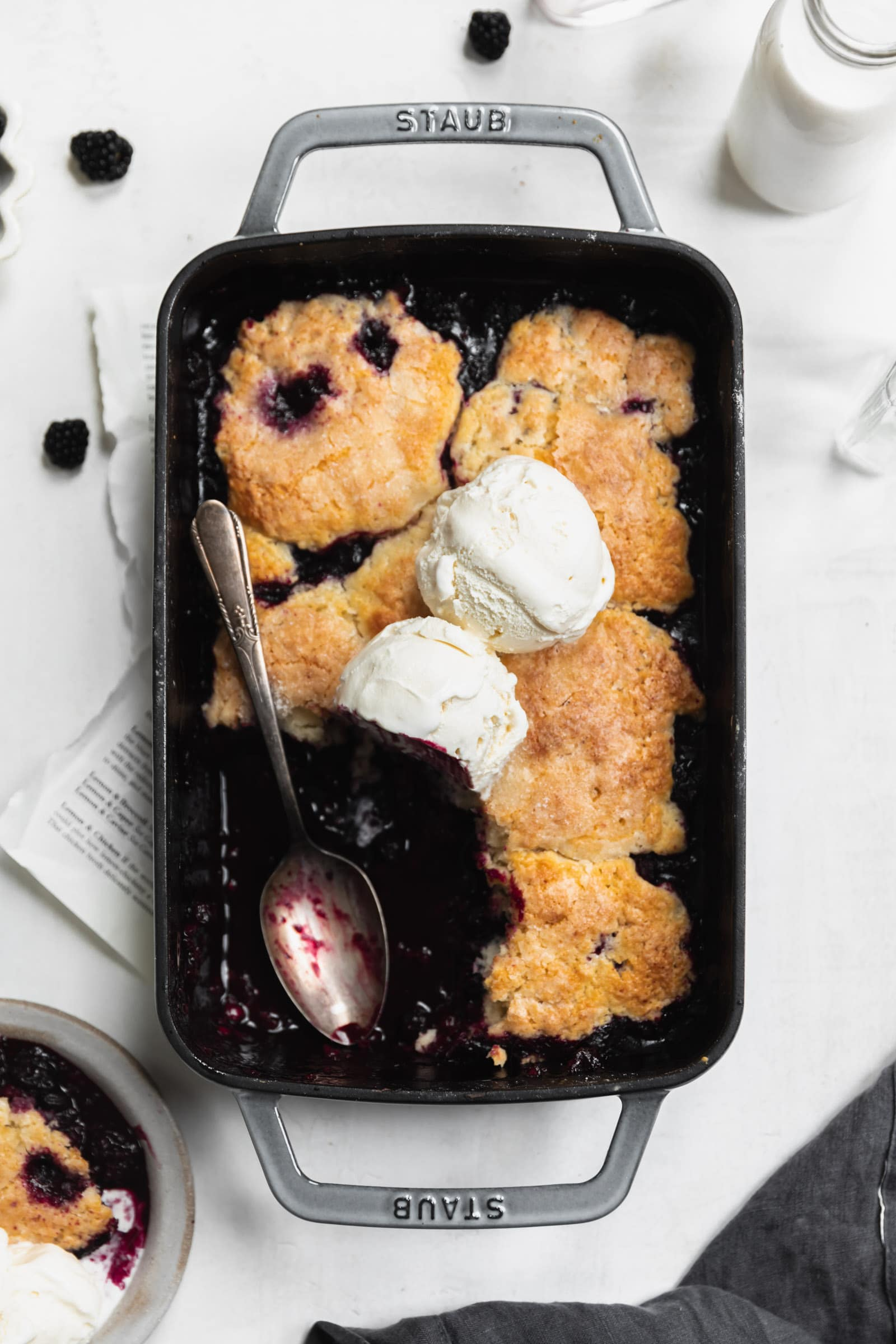 mixed berry cobbler with vanilla ice cream and spoon