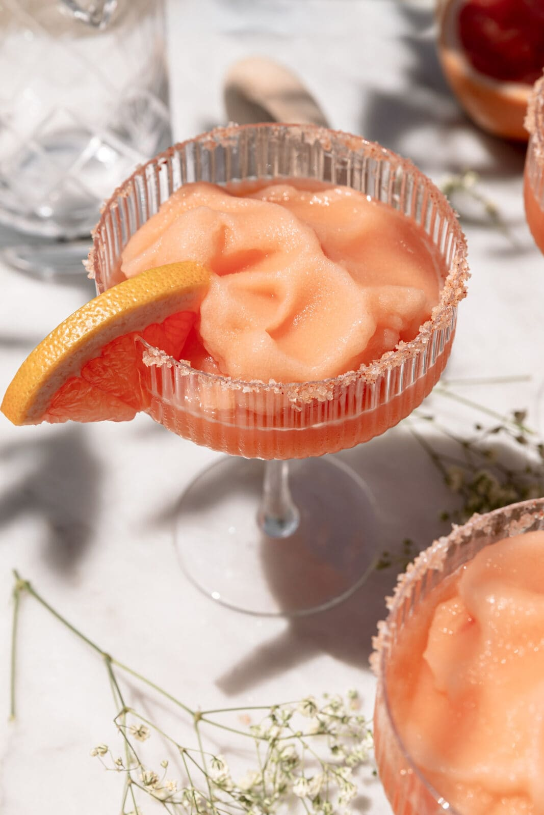 frozen paloma in a coupe glass with a salt rim