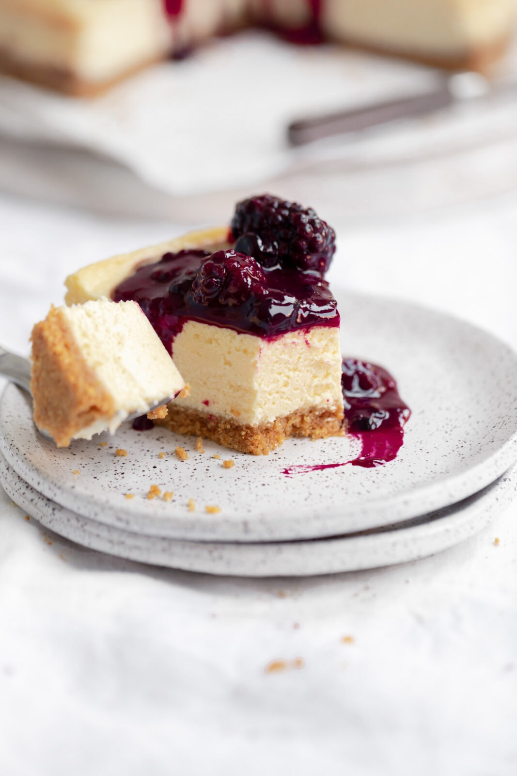 slice of cheesecake with berry compote on a plate